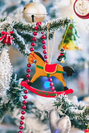 original Christmas tree toy is a wooden figurine of a horse weighing on a New Year tree. Around the red garland