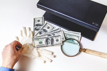 currency check is over. Hands remove rubber gloves after checking the authenticity of dollar bills. Near a large magnifier and a metal detector