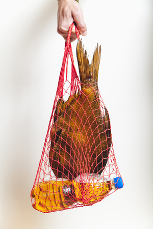 Russian tradition. Much dried fish and a plastic beer bottle lying in mesh shopping bag on a white background. Hand of man holding a weight on the net
