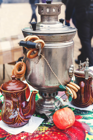 Russian set for tea. Iron samovar, clay pots, and bundle bagels standing on colorful tablecloth on a traditional Slavic holiday Maslenitsa  Standard-Bild