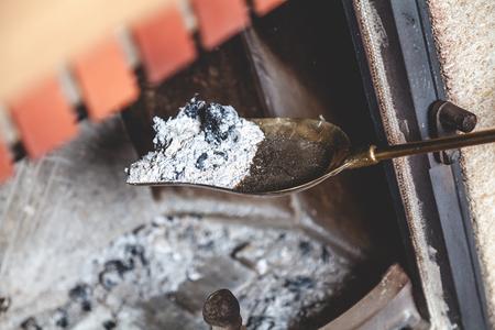 暖炉の掃除長いハンドルをクローズアップしてブレードに横たわっている灰と焦げた木片