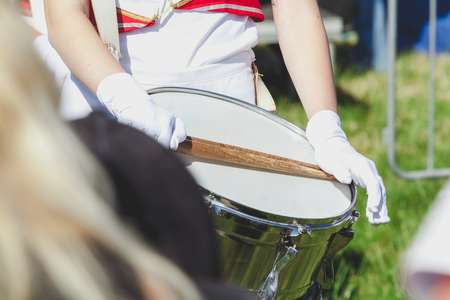 Drummer girl in school uniform uniform holds a hand in a white glove with wooden sticks on the drum membrane brilliant close-up Stock Photo