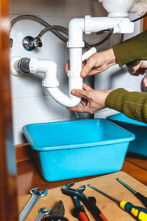 Hands apart the plumbing connections of plastic pipe kitchen hydraulic gate. Next set of tools