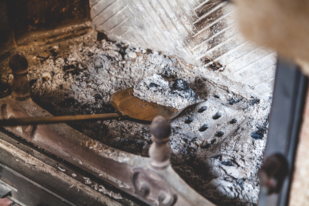 Cleaning the fireplace. Ash and charred piece of wood lying on the blade with a long handle closeup