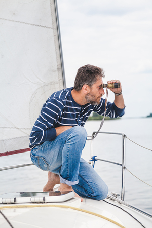 man with beard in a striped sweater and jeans sits on the bow of a sailing yacht and looks overboard with a cloudy day