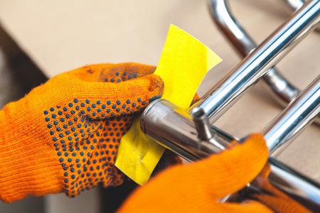 Macinazione di un portasciugamani riscaldato inossidabile. Mani in guanti arancioni puliscono la struttura metallica con carta vetrata Archivio Fotografico