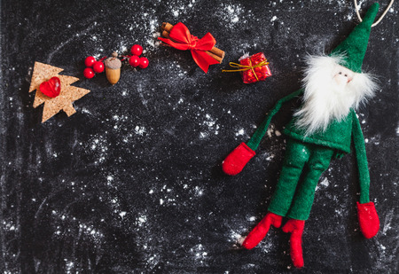 Winter plot. Soft toy of a cheerful green Santa Claus and a set of New Year objects on a dark background