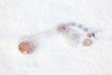 single imprint of a bare left foot on fresh white snow  Stock Photo