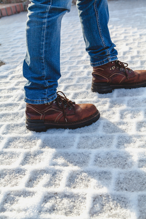 Legs in brown shoes stand on a geometric frost on a rectangular paving slab  Stock Photo