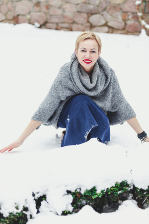 beautiful blonde in a warm sweater sits in the courtyard on a winters day and touches the snow with her hands
