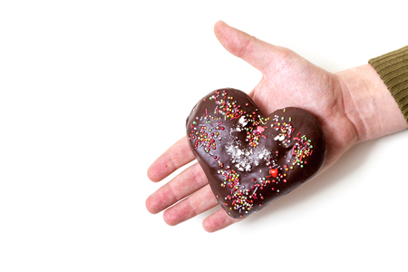 I offer my hand and my heart. Chocolate gingerbread in the form of heart lies on the palm of your hand