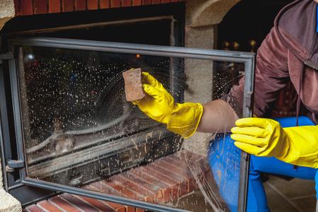 벽난로 청소. 노란색 고무 장갑에 손을 스펀지와 유리 훈제 벽난로 문을 씻으십시오 스톡 콘텐츠