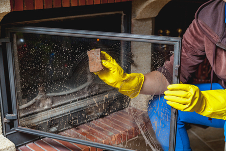 Cleaning the fireplace. Hands in yellow rubber gloves wash the glass smoked fireplace door with a sponge