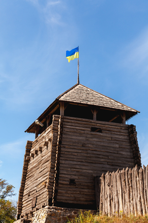 Wooden Cossack guard tower on a background of blue sky and palisade