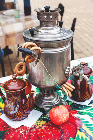 Russian set for tea. Iron samovar, clay pots, and bundle bagels standing on colorful tablecloth on a traditional Slavic holiday Maslenitsa  Stock Photo