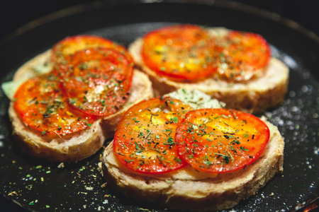 Traditional Italian sandwiches. Three bruschettes with tomatoes lie on a tray