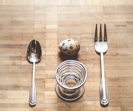 Egg quail, spiral stand, fork, spoon lie on the board. Set for dietary breakfast