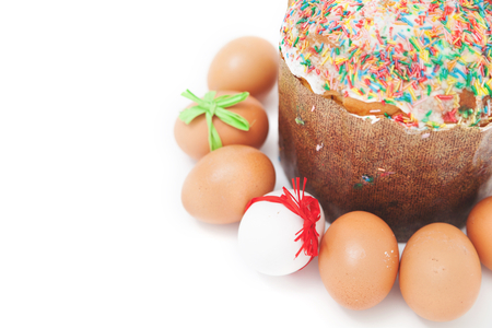 Painted Easter eggs with ribbons lie around the cake on a white background