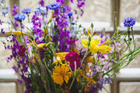 Flowers on the windowsill. A picturesque bouquet of wildflowers in a crystal vase stands against the window of transparent square glass blocks