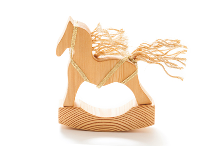 Wooden toy rocking. Figurine of a horse with a mane and tail of ropes on a white background