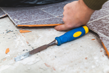 Repair of tiles. The finger is inserted into the gap between the tile and the floor. There is a chisel next to it.