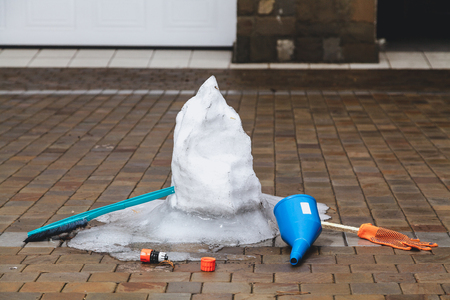 Spring in the yard. A melted snowman stands on the sidewalk tile. There is a watering can near the brush, a brush and working gloves