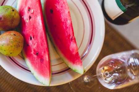 Still life with watermelon and sparkling wine. cut slices of ripe watermelon and pears lie on a plate. next to elegant glasses and a bottle of champagne