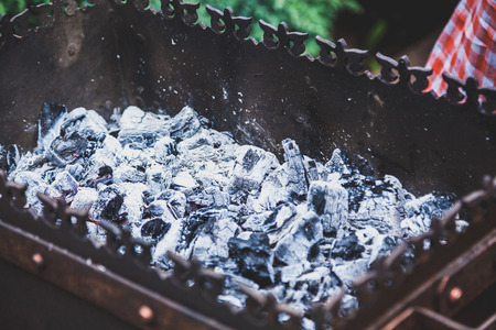 layer of hot coals in a rectangular forged brazier closeup  Stock Photo