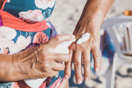Elderly woman in swimsuit smears her hands with sunscreen from a container on the summer sea beach