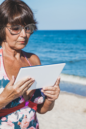 Elderly woman in a swimsuit sunbathing and holding a tablet on summer sea beach