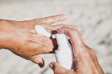 Elderly woman smears her hands with sunscreen from a container on the summer sea beach