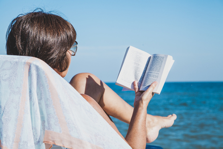 Elderly woman in a swimsuit sunbathing and reading a book on summer sea beach Stock Photo