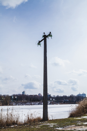 support of overhead electric power lines with broken wires stands on the bank of a frozen river