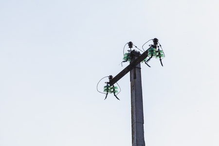 Support for overhead power lines with broken wires against the gray sky  Stock Photo