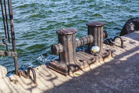 Double cast iron mooring bollard on a concrete pier on the beach a summer day close-up. Nearby is a round metal jar