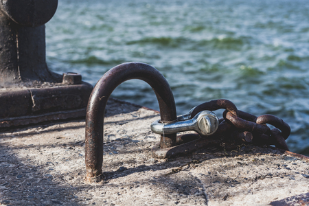 Powerful metal loop with a chain and a cast-iron mooring bollard at the edge of the concrete pier closeup