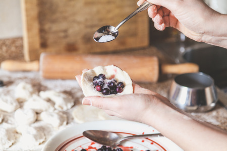 woman hand pours sugar into a raw dumpling with a stuffing of black round berries. On the table lie raw dumplings, sieve and rolling pin