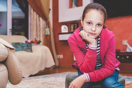 Young girl in a red sweater sitting in a cozy room
