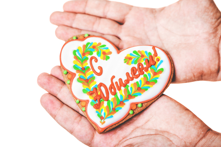gift for the anniversary. Appetizing gingerbread in the form of a heart lies on the palms of your hands. Gingerbread on an engraving With an anniversary  Reklamní fotografie