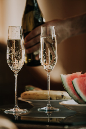 Two beautiful elegant glasses with champagne are on the table. At the back is a hand with a bottle of wine. Close slices of watermelon and banana