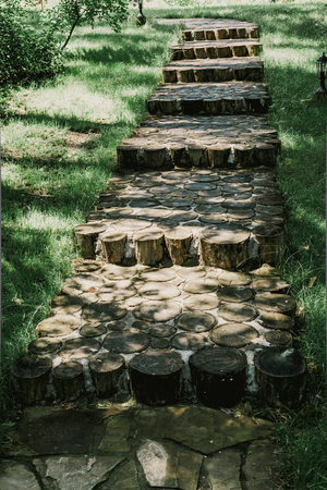 Steps from circumcised round woods driven into the ground in the middle of a green grassy lawn on a summer day