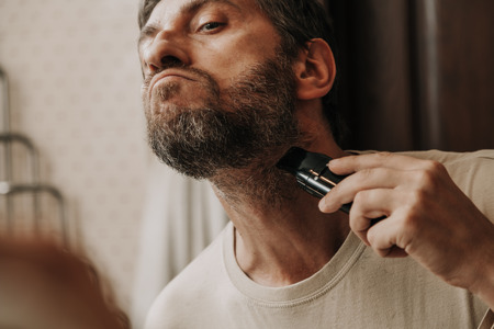 beard trimmer trimmer. The man independently cuts his gray beard with a machine