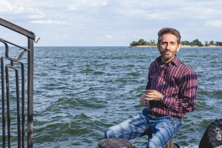 man with a beard sitting on the mooring bollard on a concrete pier and holding a flat flask on the bank of a wide river  Stock Photo
