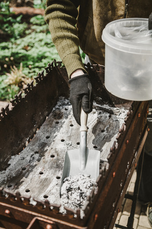 Cleaning the brazier after a picnic. Hands brush the brazier with a narrow spade. Ashes are piled in a plastic container Stock Photo