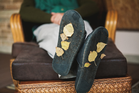 Traces of autumn. The tired man rests on the veranda in the chair. At the base of his house slippers, yellow autumn leaves stuck.