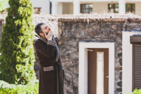 Summer morning in the courtyard. A man with a beard in a brown robe sweetly yawns into the courtyard of the estate in the early morning Stok Fotoğraf