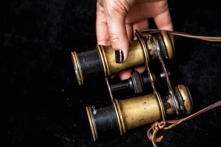 Binoculars and a woman. Beautiful female hands with manicure hold vintage metal binoculars Imagens