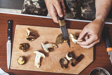 Processing of collected mushrooms. Hands of a man cut fresh edible porcini mushrooms on a wooden board 写真素材