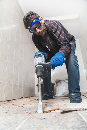 man with a beard in a checkered shirt destroys the floor tiles with a construction puncher. Bottom view Reklamní fotografie