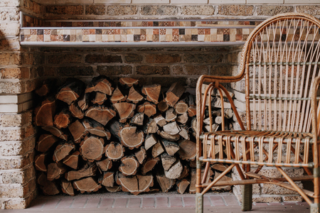 Autumn story light beautiful wicker chair from rattan stands on an empty veranda from behind lies a stack of punctured firewood.